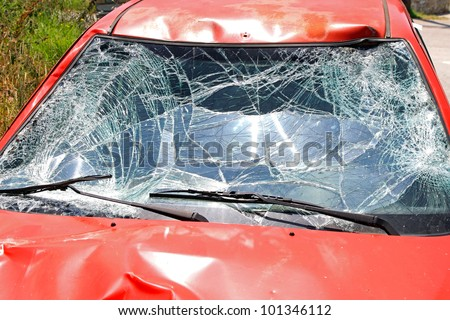 Broken windscreen at red car in traffic accident - stock photo
