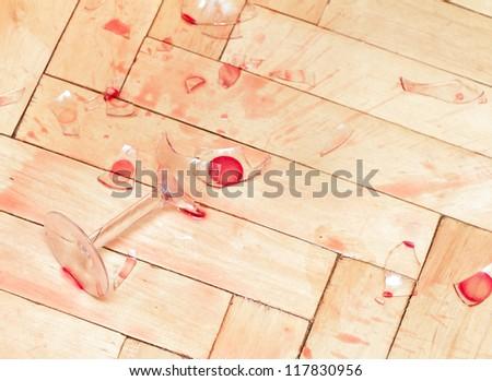 Broken wine glass on the parquet. - stock photo