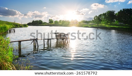 Broken wooden pier on a river at sunrise - stock photo
