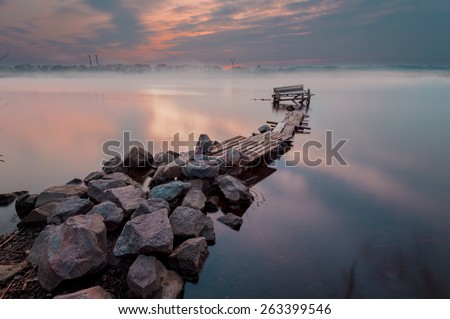 broken wooden pier on a spring river in sunset time. Stone dam on foreground. Long exposure shot - stock photo
