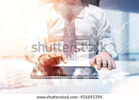 Broker consultant with charts using tablet at office desk to make a stock exchange deal. Double exposure - stock photo