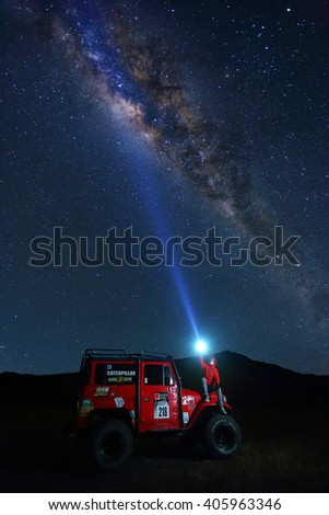 BROMO, INDONESIA - JUN 22: Unidentified tourists sitting on 4x4 Jeep for rent with light shines above the milky way in night at Mount Bromo on June 22, 2015 in Java, Indonesia.  - stock photo