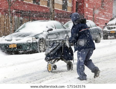 BRONX, NEW YORK - JANUARY 21: A mail man works while weathering a 6 to 10 inch snow storm and teen temperatures along Ogden avenue and 162nd street.  Taken January  21,  2014 in the Bronx,  New York. - stock photo