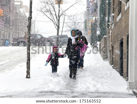BRONX, NEW YORK - JANUARY 21: A small child and mother weathering a 6 to 10 inch snow storm and teen temperatures along Ogden avenue and 162nd street.  Taken January  21,  2014  the Bronx,  New York. - stock photo