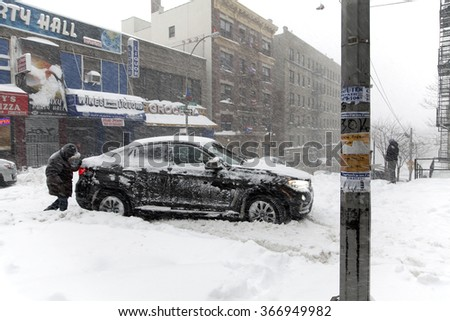 BRONX, NEW YORK - JANUARY 23: Man pushes stuck auto on Anderson Avenue street during Blizzard storm Jonas.  Taken January 23, 2016, in the Bronx,  New York.