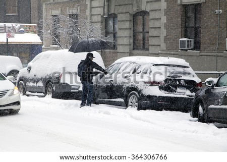 BRONX, NEW YORK, USA - MARCH 3: Man cleans his car during snow storm.  Taken March 3, 2015 in the Bronx,  New York. - stock photo