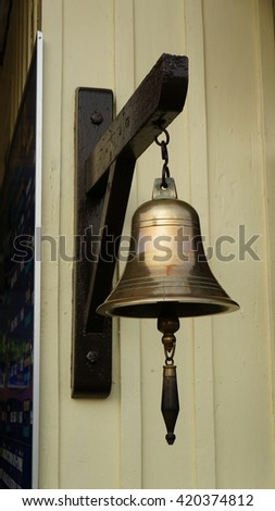 Bronze Bell hanging on wooden dark hook at bright wooden wall. Photo taken at a train station in Thailand. - stock photo