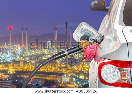 Bronze car at gas station being filled with fuel and the blurred oil refinery with tube and oil tank along night sky at Si Racha District background, Transportation Concept, selective focus  - stock photo