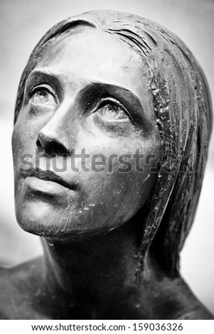 Bronze face  of tombstone sculpture - stock photo