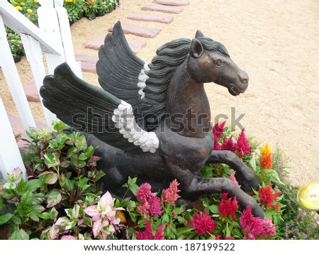Bronze horse statue among flowers in the garden.
