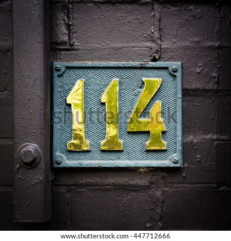 Bronze house number one hundred and fourteen - stock photo