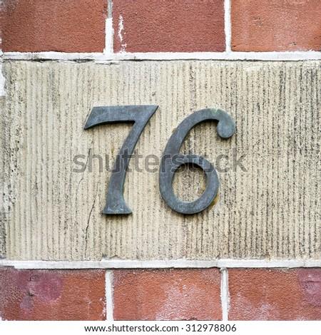 Bronze house number seventy six. - stock photo