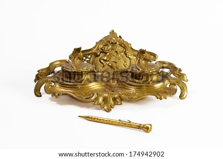 Bronze inkstand and gold pencil - stock photo
