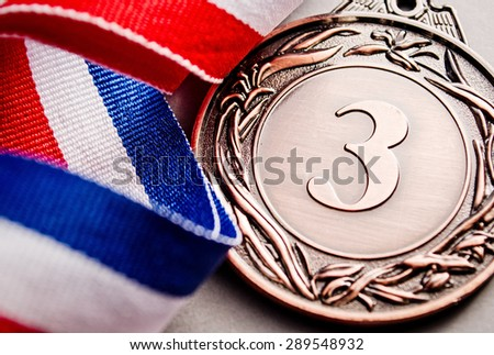 Bronze medal in the foreground on three-colour ribbon - stock photo