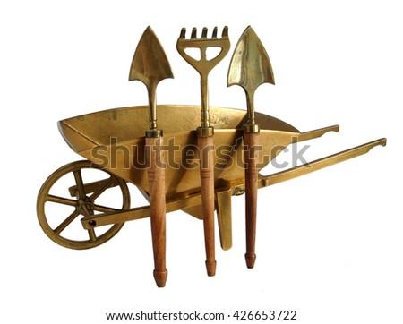 Bronze miniature wheelbarrow with shovels and rakes isolated on white background                                 - stock photo