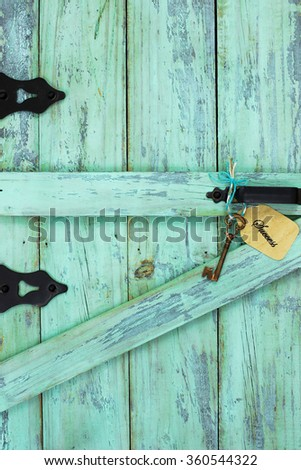 Bronze skeleton key and Success tag hanging on antique mint green rustic wood door - stock photo