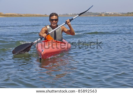 Bronzed man riding by kayak - stock photo