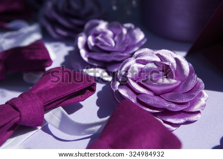 brooch handmade silk ribbons in the form of a violet  flower and bow tie at the wedding reception - stock photo