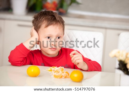 Brooding boy cleans tangerines