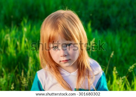 brooding red-haired girl on the background of green grass - stock photo