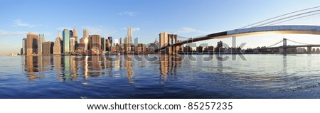 Brooklyn Bridge and Manhattan Bridge with lower Manhattan skyline panorama over East River in New York City - stock photo
