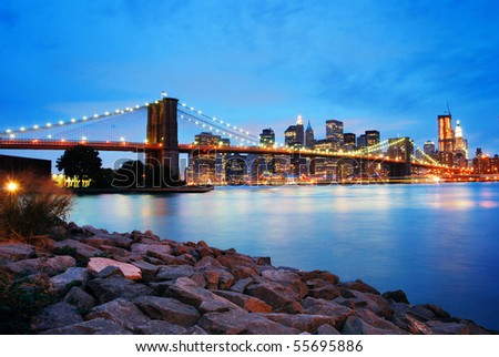 Brooklyn Bridge and Manhattan skyline in New York City over Hudson River at night.