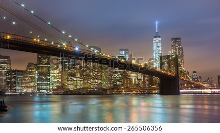 Brooklyn bridge and New York City Manhattan downtown skyline at dusk with skyscrapers illuminated over East River panorama. - stock photo