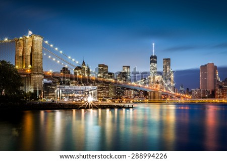 Brooklyn Bridge and the Lower Manhattan at dusk. A boat leaves light trails on East River.