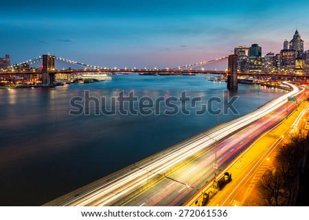 Brooklyn Bridge and with traffic trails on the FDR drive at dusk - stock photo