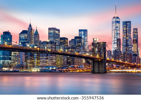Brooklyn Bridge at and the Lower Manhattan skyline under a purple sunset - stock photo