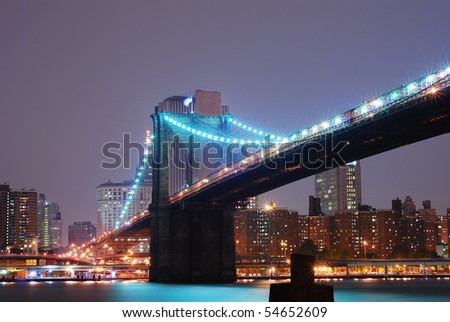 Brooklyn bridge at night with New York City skyline over Hudson River. - stock photo