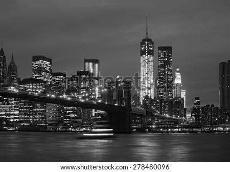 Brooklyn Bridge, East River and Manhattan at night with lights and reflections. New York City - stock photo