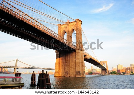 Brooklyn Bridge over East River viewed from New York City Lower Manhattan waterfront at sunset. - stock photo