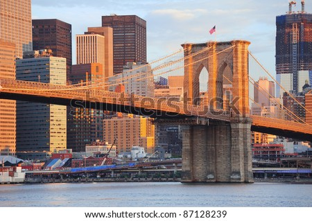 Brooklyn Bridge with lower Manhattan skyline in the morning with colorful cloud over East River in New York City - stock photo