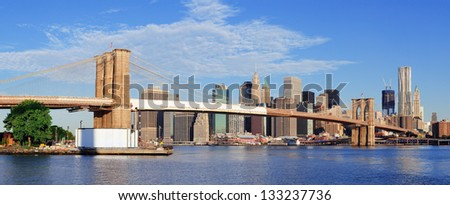 Brooklyn Bridge with lower Manhattan skyline panorama in the morning with  cloud and blue sky over East River in New York City - stock photo