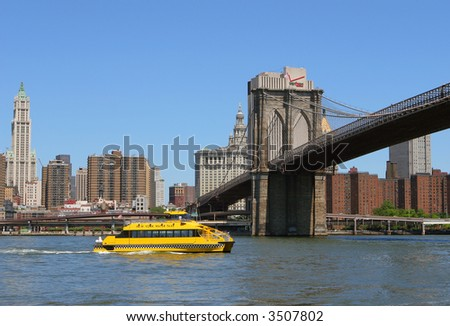 Brooklyn Bridge with Manhattan Skyline and a Water Taxi - stock photo
