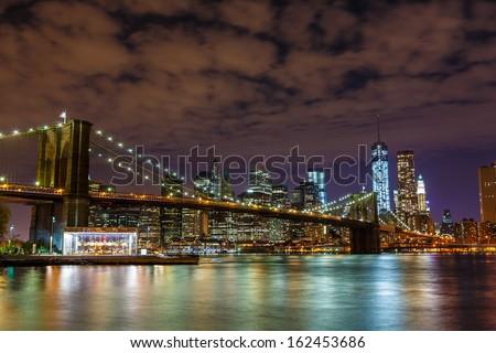 Brooklyn Bridge with Manhattan skyline in the background at night - stock photo