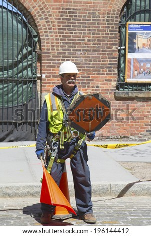 BROOKLYN, NEW YORK - APRIL 24  Construction worker regulates traffic in Dumbo section of Brooklyn on April 24, 2014. Dumbo is a neighborhood in the New York City borough of Brooklyn - stock photo