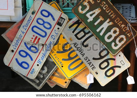 BROOKLYN, NEW YORK - AUGUST 13, 2017: Old car license plates at Brooklyn's largest flea market in DUMBO. In the U.S., where each state issues plates, New York State has required plates since 1901