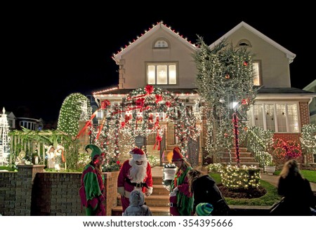 "BROOKLYN, NEW YORK, USA - DECEMBER 19: Child visits Christmas house with Santa ""Vincent Privitelli"" in Dyker Heights. Donations raised for Alzheimer's awareness. Taken December 19, 2015 in New York."