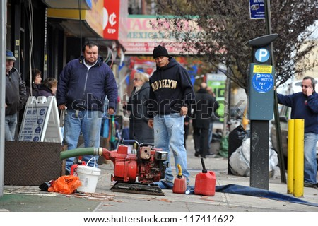 BROOKLYN, NY - NOVEMBER 01: People pumping water out buildings at the Brighton Beach neighborhood due to impact from Hurricane Sandy in Brooklyn, New York, U.S., on Thursday, November 01, 2012. - stock photo