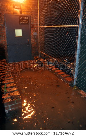 BROOKLYN, NY - OCTOBER 29: Flooded building entrance, caused by Hurricane Sandy, are seen on October 29, 2012, in the corner of Bragg street and  Shore Pway of Brooklyn NY, United States. - stock photo