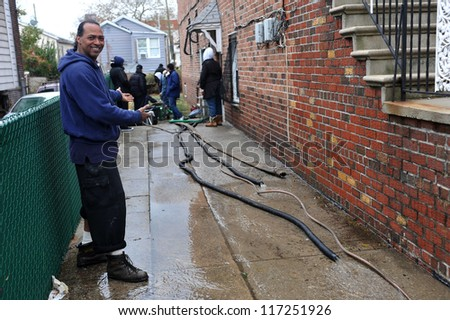 BROOKLYN, NY - OCTOBER 30: People pumping water out of building basement in the Sheapsheadbay neighborhood due to flooding from Hurricane Sandy in Brooklyn, New York, U.S., on October 30, 2012. - stock photo