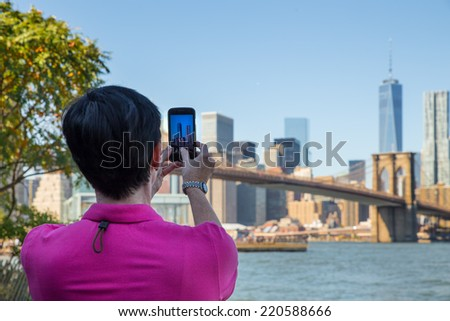 BROOKLYN, NY - SEPTEMBER 27, 2014:  Visitor at Brooklyn Bridge Park photographing the Brooklyn Bridge and New York City skyline using an iPhone.   - stock photo