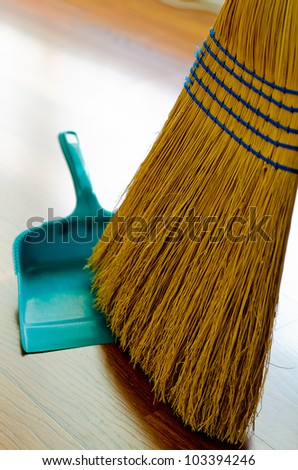 Broom and dust pan on hardwood floor. - stock photo