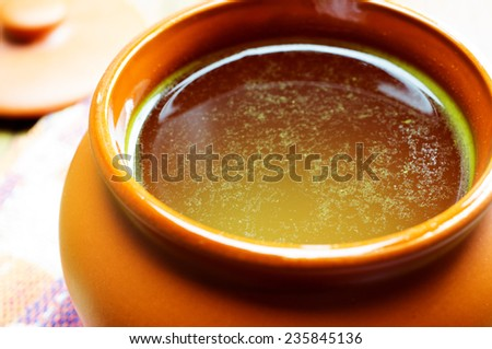 Broth, bouillon, clear soup in a clay pot, close-up - stock photo