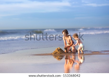 Brother and baby sister building a sand castle having fun together at a sea shore at beautiful sunset in summer - stock photo