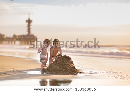 Brother and baby sister building a sand castle together at a beautiful beach in Holland at sunset on a warm summer evening - stock photo