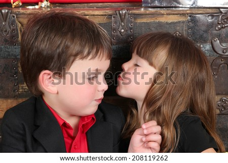 Brother and sister against a wooden background on christmas day - stock photo
