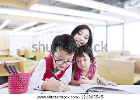 Brother and sister are drawing with their teacher in classroom